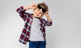 Красивый мальчик в рубашке шотландки, серой рубашке и джинсах стоит на серой предпосылке Мальчик в черных солнечных очках Мальчик Стоковые Фотографии RF