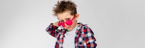 Красивый мальчик в рубашке шотландки, серой рубашке и джинсах стоит на серой предпосылке Мальчик в красных солнечных очках Мальчи стоковое фото rf
