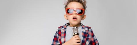 Красивый мальчик в рубашке шотландки, серой рубашке и джинсах стоит на серой предпосылке Солнечные очки мальчика нося Рыжеволосый стоковое изображение