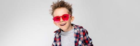 Красивый мальчик в рубашке шотландки, серой рубашке и джинсах стоит на серой предпосылке Мальчик в красных солнечных очках Мальчи стоковая фотография