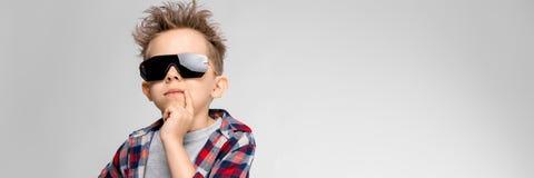 Красивый мальчик в рубашке шотландки, серой рубашке и джинсах стоит на серой предпосылке Мальчик в черных солнечных очках Мальчик стоковое фото rf