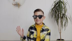 Красивый мальчик в солнечных очках сидит на поле на фоне белой стены и держит воздушный шар акции видеоматериалы