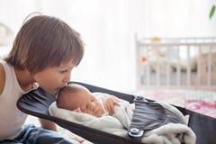 Красивый мальчик, обнимающ с нежностью и заботит его newborn младенец Стоковое Изображение RF