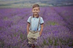 Красивый мальчик при светлые волосы нося голубую футболку и стильные шорты при виселица шкивов представляя на лете field вполне л Стоковая Фотография RF