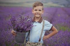 Красивый мальчик при светлые волосы нося голубую футболку и стильные шорты при виселица шкивов представляя на лете field вполне л Стоковые Фотографии RF