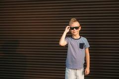 Красивый мальчик усмехаясь и представляя к фотографу Радостный ребенок идет парк Солнечное лето погоды стоковое изображение