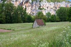 Красивый маленький каменный дом в середине цвести зеленая предпосылка времени поля весной Стоковые Фотографии RF