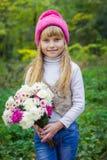 Красивый маленький молодой младенец в розовой шляпе с цветками в их руках стоковые изображения