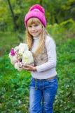 Красивый маленький молодой младенец в розовой шляпе с цветками в их руках стоковые изображения rf