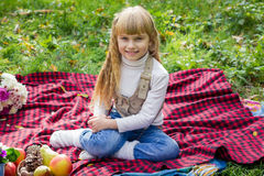 Красивый маленький молодой младенец сидя на красной шотландке Симпатичный ребенок усмехаясь с яркими цветками Стоковые Изображения RF