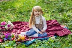 Красивый маленький молодой младенец сидя на красной шотландке Симпатичный ребенок усмехаясь с яркими цветками Стоковые Фото