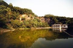 Красивый маленький дом озером на предпосылке гор покрытых с деревьями Стоковые Фото