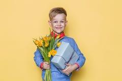 Красивый мальчик держа пук и подарочную коробку цветка Валентайн дня s День рождения мать s дня Портрет студии над желтой предпос Стоковое фото RF
