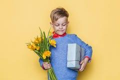 Красивый мальчик держа пук и подарочную коробку цветка Валентайн дня s День рождения мать s дня Портрет студии над желтой предпос Стоковая Фотография
