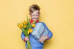 Красивый мальчик держа пук и подарочную коробку цветка Валентайн дня s День рождения мать s дня Портрет студии над желтой предпос Стоковое Изображение RF