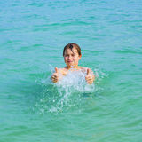 Красивый мальчик имеет потеху в океане и показывает большие пальцы руки вверх стоковые изображения rf
