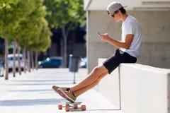 Красивый мальчик конькобежца используя его мобильный телефон в улице Стоковая Фотография RF
