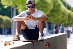 Красивый мальчик конькобежца используя его мобильный телефон в улице Стоковые Фотографии RF