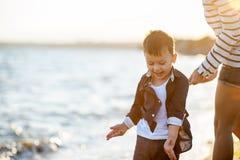 Красивый мальчик при женщина ослабляя на пляже Стоковая Фотография
