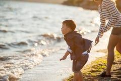 Красивый мальчик при женщина ослабляя на пляже Стоковое фото RF