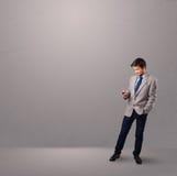 Красивый мальчик стоя и держа телефон Стоковое Фото