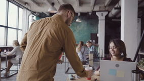 Красивый менеджер бизнесмена приходит к современному офису на работе Молодой мужчина приветствует с коллегами, приносит кофе к др сток-видео
