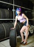 Красивый механик автомобиля девушки битника работает с автошинами на колесах Стоковые Изображения