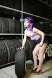 Красивый механик автомобиля девушки битника работает с автошинами на колесах Стоковые Изображения RF