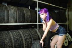 Красивый механик автомобиля девушки битника работает с автошинами на колесах Стоковое Фото