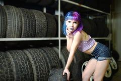 Красивый механик автомобиля девушки битника работает с автошинами на колесах Стоковое Изображение