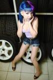 Красивый механик автомобиля девушки битника работает с автошинами на колесах Стоковые Фотографии RF