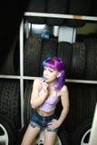 Красивый механик автомобиля девушки битника работает с автошинами на колесах Стоковые Фото