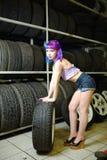Красивый механик автомобиля девушки битника работает с автошинами на колесах Стоковое Изображение RF