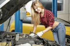 Красивый механик девушки ремонтируя автомобиль Стоковое Изображение
