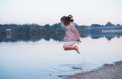 Красивый младенец с вьющиеся волосы жизнерадостно скачет на банк озера Активная прогулка весны на открытом воздухе стоковое фото rf