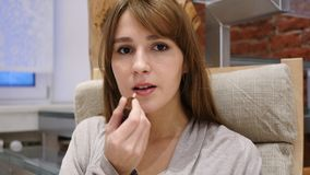 Красивый модельный применяясь состав на ее стороне, кладя на губную помаду Стоковая Фотография