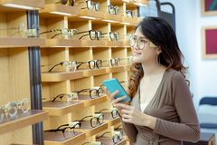Красивый молодой азиатский смартфон удерживания женщины для покупки онлайн стекел стоковая фотография rf