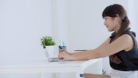 Красивый молодой азиатский усмехаться женщины говорит здравствуйте используя сеть болтовни социальную с видео- звонком на ноутбук