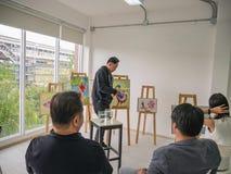Красивый молодой азиатский художник цвета человека или воды уча как покрасить в студии стоковые изображения rf