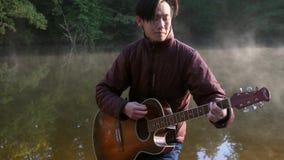 Красивый молодой азиатский человек играя гитару на побережье реки леса на восходе солнца Туман рассвета туманный на предпосылке сток-видео