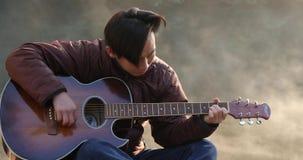 Красивый молодой азиатский человек играя гитару на побережье реки леса на восходе солнца Туман рассвета туманный на предпосылке видеоматериал