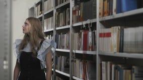 Красивый молодой белокурый студент ища книга в школьной библиотеке акции видеоматериалы
