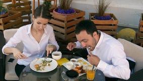 Красивый молодой бизнесмен имея еду с партнером в ресторане Стоковое фото RF