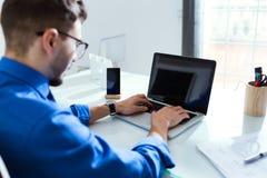 Красивый молодой бизнесмен работая с компьтер-книжкой в офисе Стоковые Фото