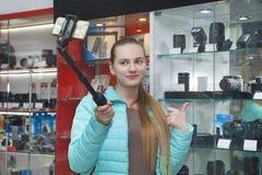 Красивый молодой блоггер в профессиональном магазине оборудования фото рекламирует оборудование фото используя ручку и телефон se стоковые фото