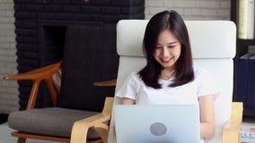 Красивый молодой женщины портрета азиатской работая онлайн компьтер-книжка с улыбкой и счастливым усаживанием на софе акции видеоматериалы