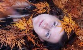 Красивый молодой индивидуал, эксцентричная женщина, с интересным стилем причесок, dreadlocks, прошивка и татуировка, лежат в саде стоковое изображение rf