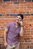 Красивый молодой кавказский человек с мобильным телефоном и назад шляпой усмехаясь для портретов перед текстурированным снаружи к стоковое фото rf