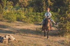 Красивый молодой мальчик с красными волосами и голубые глазы играя с его пони лошади друга в forestHuge любят между shild ребенк  Стоковое фото RF