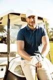 Красивый молодой мужской игрок в гольф с отдыхать клуба стоковое фото rf